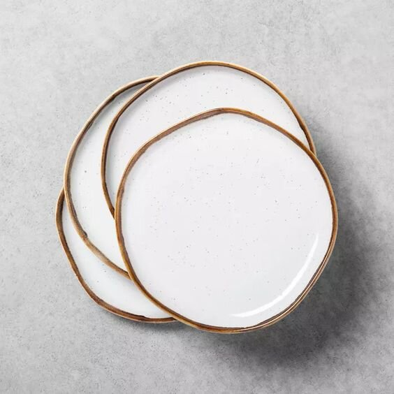 Modern white glazed ceramic plates with raw uncoated edge for a chic table setting.jpg