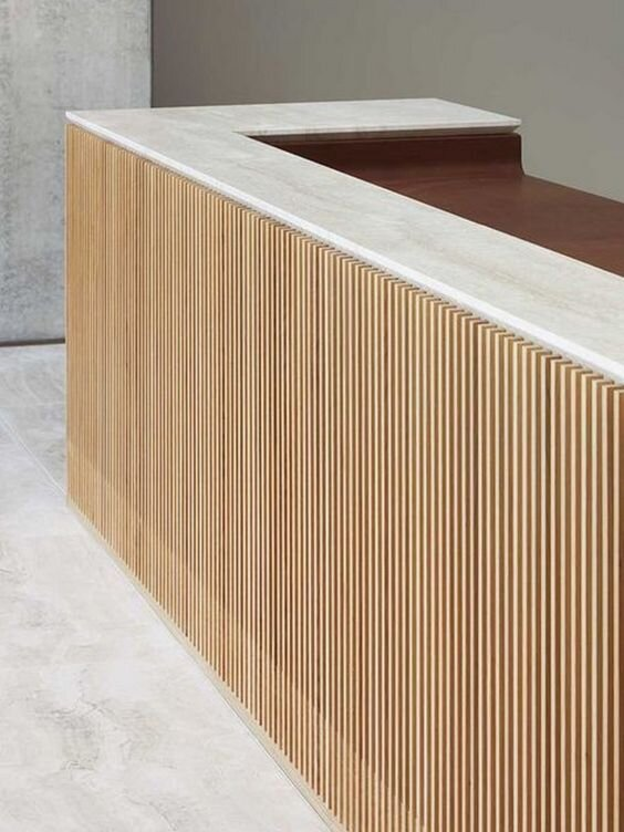 stone and slatted wood panneled reception desk - interior design trends 2020 and 2019.jpg