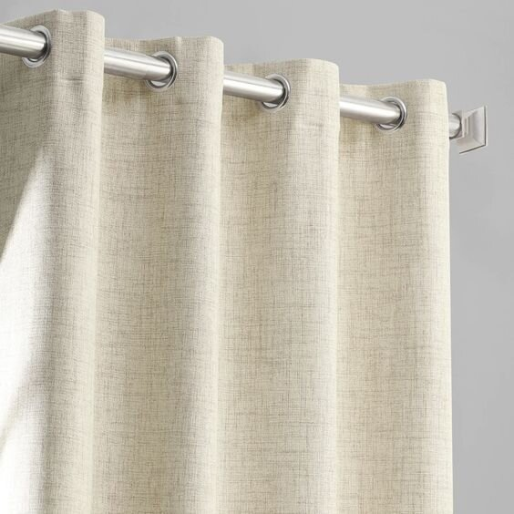 Modern beige grommet curtains for a contemporary living room - pros and cons of different drapery styles by the savvy heart.jpg