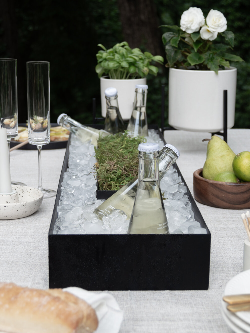 Bottles of champagne in a tabletop planter - chic dining al fresco date night.jpg