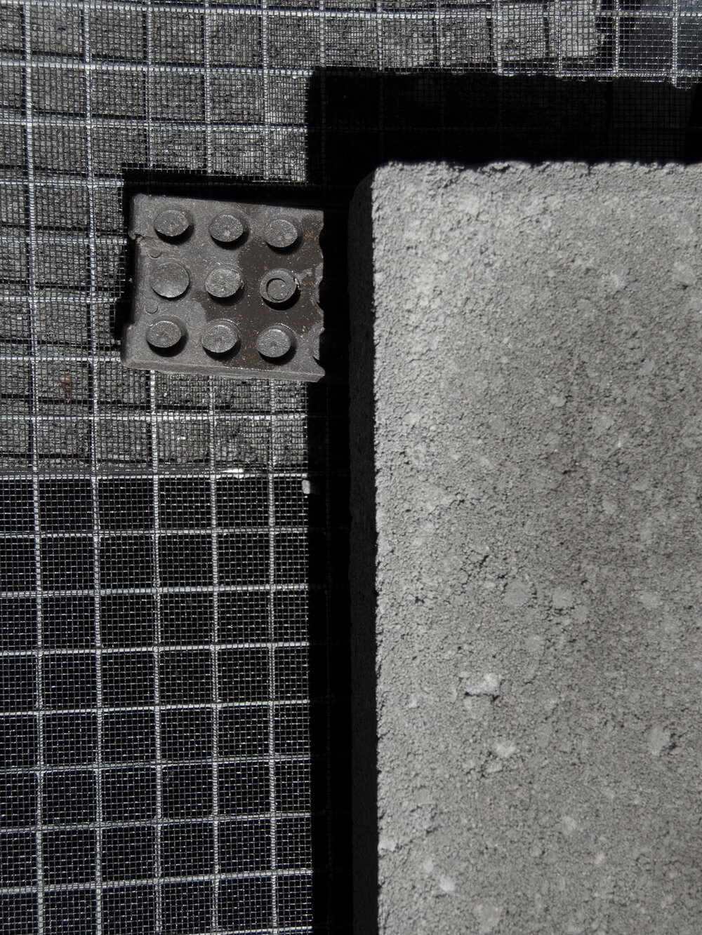 Shims under a paver for a DIY bubbling fountain.jpg