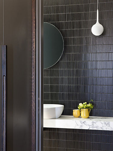 warm and moody bathroom with stacked tile behind the sink