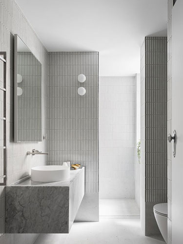 White stacked tile bathroom with tiled walls